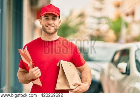 Young caucasian deliveryman smiling happy holding delivery paper bag at the city.