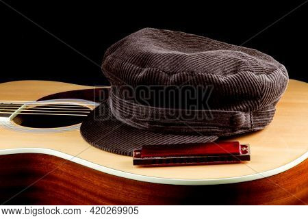 Corduroy Cap With Acoustic Guitar And Harmonica On A Black Background