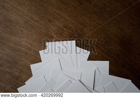 Stack Of A Blank Business Card On A Dark Wooden Background. View From Above. Layout For Creating A C