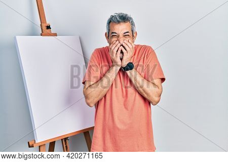 Handsome middle age man with grey hair standing by painter easel stand laughing and embarrassed giggle covering mouth with hands, gossip and scandal concept