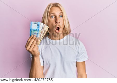 Caucasian young man with long hair holding hungarian forint banknotes scared and amazed with open mouth for surprise, disbelief face