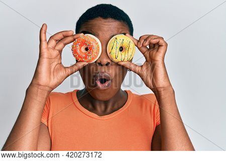 Young african american woman holding tasty colorful doughnuts on eyes afraid and shocked with surprise and amazed expression, fear and excited face.