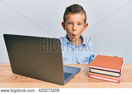 Adorable caucasian kid studying for school exam using laptop scared and amazed with open mouth for surprise, disbelief face