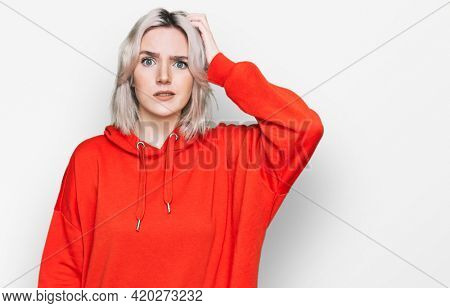 Young blonde girl wearing casual clothes confuse and wonder about question. uncertain with doubt, thinking with hand on head. pensive concept.