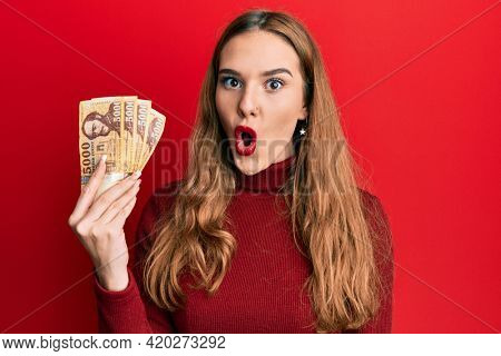 Young blonde woman holding 5000 hungarian forint banknotes scared and amazed with open mouth for surprise, disbelief face