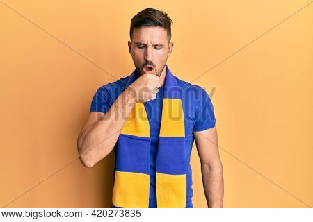 Handsome man with beard football hooligan cheering game feeling unwell and coughing as symptom for cold or bronchitis. health care concept.