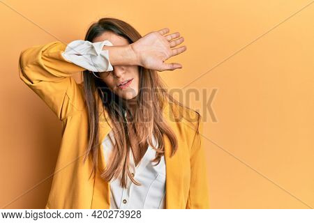 Young beautiful woman wearing business style and glasses covering eyes with arm, looking serious and sad. sightless, hiding and rejection concept