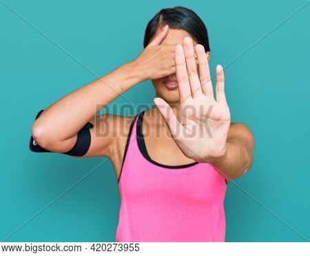 Beautiful asian young sport woman wearing sportswear and arm band covering eyes with hands and doing stop gesture with sad and fear expression. embarrassed and negative concept.