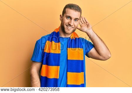 Young caucasian man football hooligan cheering game smiling with hand over ear listening and hearing to rumor or gossip. deafness concept.