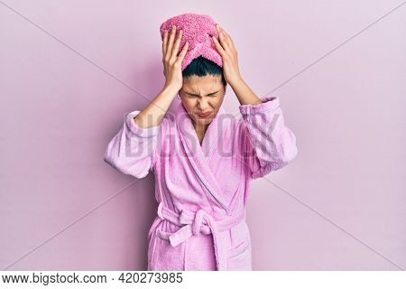 Young hispanic woman wearing shower towel cap and bathrobe suffering from headache desperate and stressed because pain and migraine. hands on head.