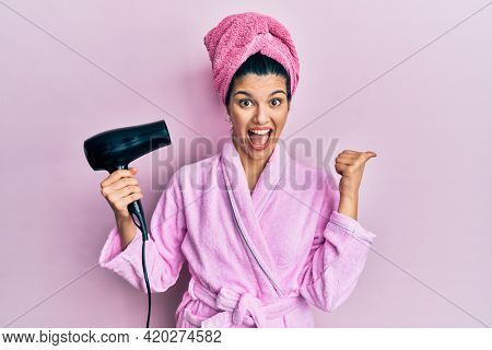 Young hispanic woman wearing shower bathrobe using dryer pointing thumb up to the side smiling happy with open mouth