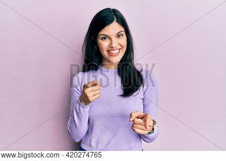 Young hispanic woman wearing casual clothes pointing fingers to camera with happy and funny face. good energy and vibes.