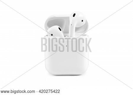 Modern Wireless Earbuds Headphones Lying In A Charging Case Isolated On White Background.