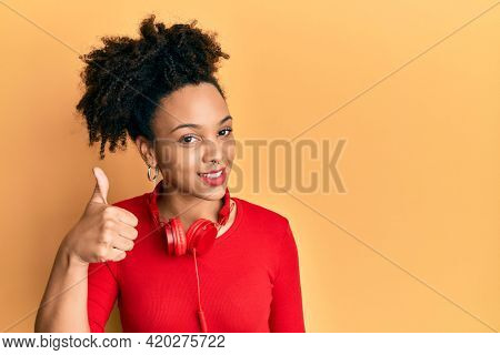 Young african american girl listening to music using headphones smiling happy and positive, thumb up doing excellent and approval sign
