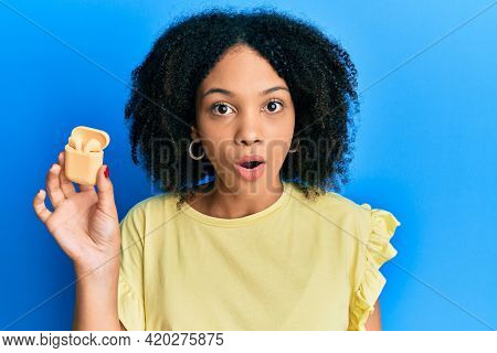 Young african american girl listening to music using earphones scared and amazed with open mouth for surprise, disbelief face