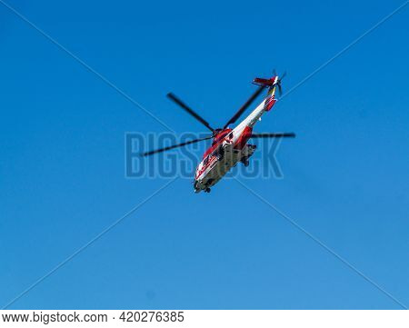 Red Rescue Helicopter Moving In Blue Sky. Rapid Medical Assistance Or Rescue By Helicopter
