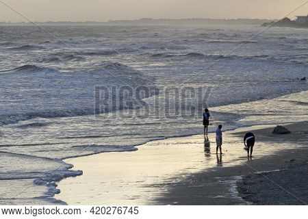 Silhouetted Beachcombers Wander The Beach And Wade In The Choppy Surf On A Moody Day At Folly Beach,