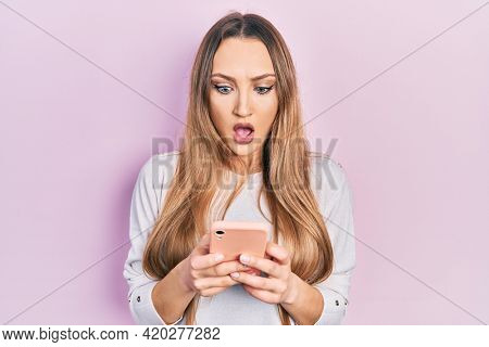 Young blonde girl using smartphone typing message afraid and shocked with surprise and amazed expression, fear and excited face.