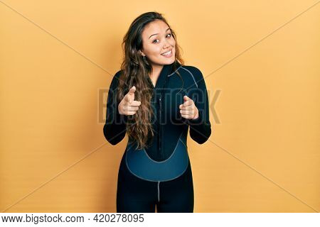 Young hispanic girl wearing diver neoprene uniform pointing fingers to camera with happy and funny face. good energy and vibes.