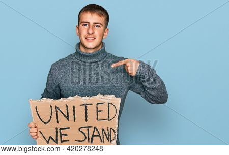 Young blond man holding united we stand banner pointing finger to one self smiling happy and proud