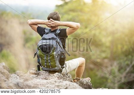 The Adventurous Traveler Do A Relaxed Sitting Posture On The Cliff In The Evening. Concept Outdoors