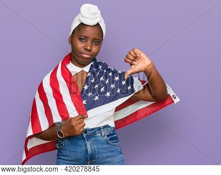 Young african woman with turban holding united states flag with angry face, negative sign showing dislike with thumbs down, rejection concept