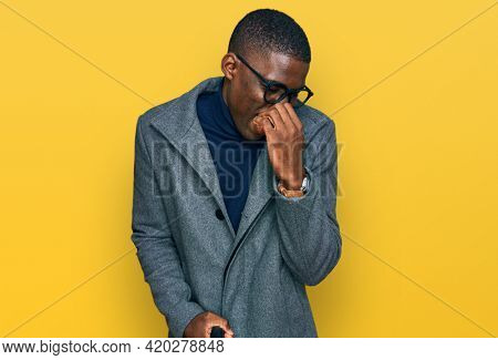 Young african american man wearing business clothes and glasses smelling something stinky and disgusting, intolerable smell, holding breath with fingers on nose. bad smell
