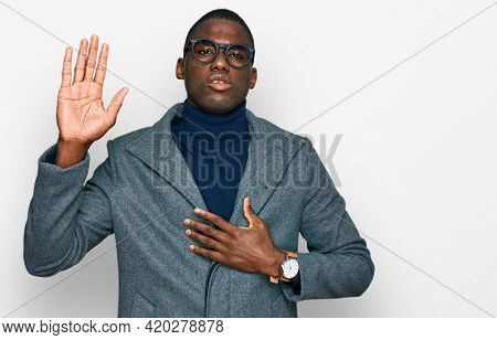 Young african american man wearing business clothes and glasses swearing with hand on chest and open palm, making a loyalty promise oath