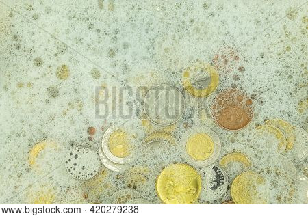 Money Laundering Concept, Coins In Soapy Water. Money Laundering, Coins Of Different Denominations A