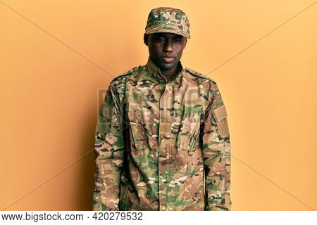 Young african american man wearing army uniform looking sleepy and tired, exhausted for fatigue and hangover, lazy eyes in the morning.
