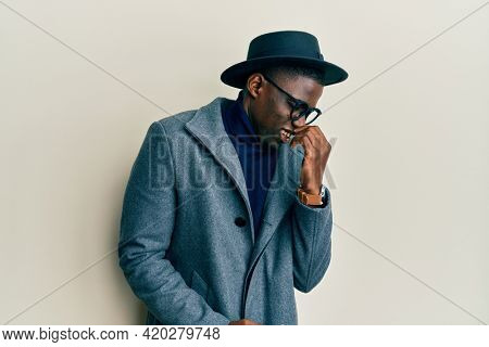 Young african american man wearing elegant style smelling something stinky and disgusting, intolerable smell, holding breath with fingers on nose. bad smell