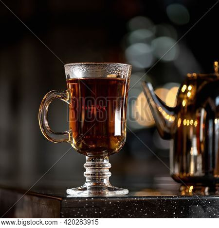 Hot Black Tea In Glass Cup With Handle Backlit On Black Background. Side View. Soft Focus.