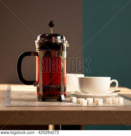 Brewed Black Tea. Full Teapot Or French Press Of Hot Drink On Wooden Table With Teacup And Lumps Of