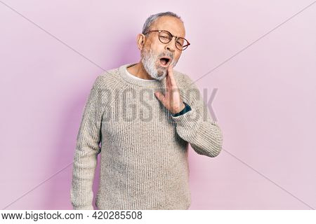 Handsome senior man with beard wearing casual sweater and glasses touching mouth with hand with painful expression because of toothache or dental illness on teeth. dentist