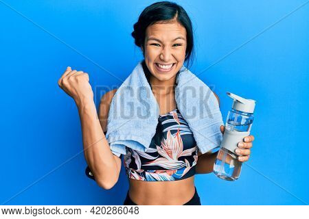 Beautiful hispanic woman wearing sportswear holding water bottle screaming proud, celebrating victory and success very excited with raised arm