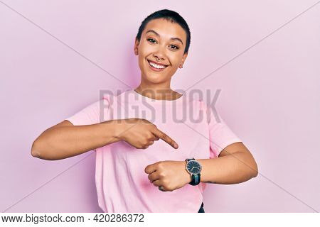 Beautiful hispanic woman with short hair wearing casual pink t shirt in hurry pointing to watch time, impatience, upset and angry for deadline delay