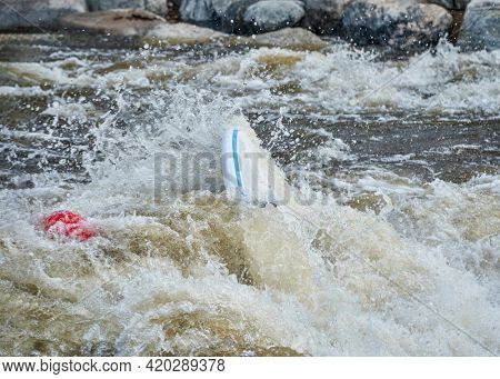 surfer swimming with surfboard after surfing a wave in the Poudre River Whitewater Park.
