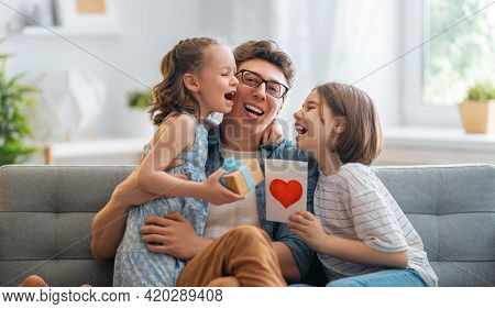 Children daughters are congratulating their father and giving him postcard. Dad and girls are smiling and hugging. Family holiday and togetherness.