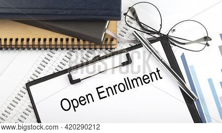 Text Open Enrollment On Office Desk Table With Notebooks, Supplies,analysis Chart, On White Backgrou