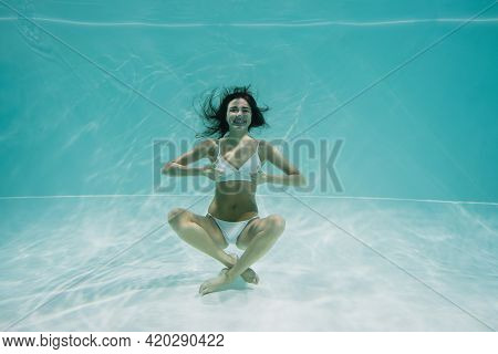 Happy Young Woman In White Swimwear Showing Thumbs Up While Swimming In Pool.