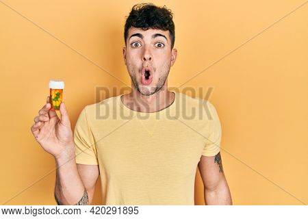 Young hispanic man holding pills scared and amazed with open mouth for surprise, disbelief face