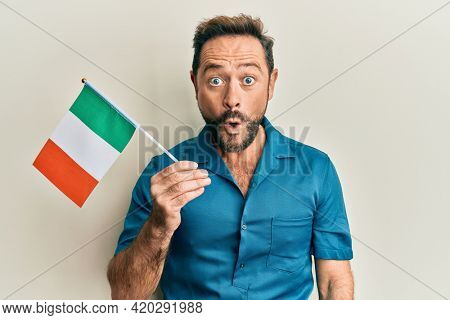 Middle age man holding ireland flag scared and amazed with open mouth for surprise, disbelief face
