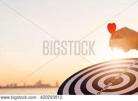 Hand Hold Of Dart Arrow On Bullseye (bull's-eye) Dartboard Is The Target Of Purpose Challenge Busine