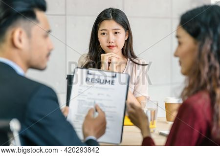 Young Asian Woman Graduate Interviewing With Two Manager When Discuss About Her Resume With Serious