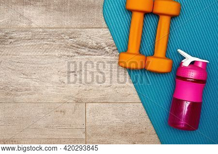 Fitness Dumbbell, Sports Mat, And Bottle On The Gym Floor. Bodycare And Healthy Lifestyle Concept