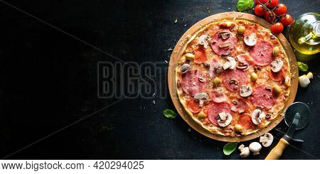Crispy italian pizza with salami, ham, olives, tomatoes, peppers, cheese and mushrooms on dark background