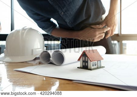 Engineer Sketching A Building Project Design With Mockup House Model And Blueprints. Architect Man W