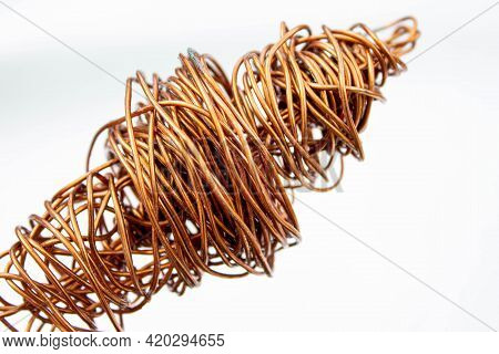 Copper Wire . The Wire Coil Is Rolled Up. The Red Copper Wire Is Crumpled. Close-up On A White Backg