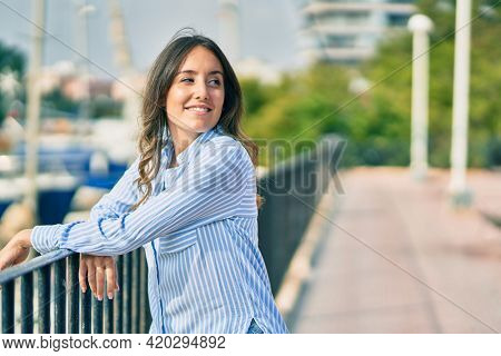 Young hispanic woman smiling happy leaning on the balustrade at the city.