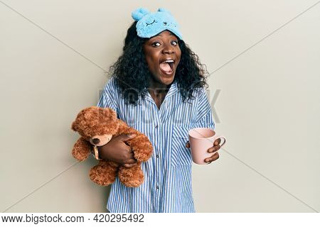 Beautiful african young woman wearing pajama, holding teddy bear and drinking coffee celebrating crazy and amazed for success with open eyes screaming excited.